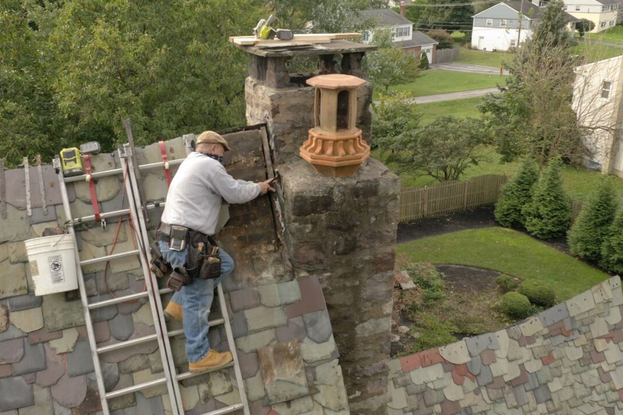 roofer repairing chimney flashing on a slate roof in King of Prussia Pa